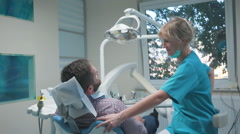 Dentist comes in to dental room, sits down and talks with patient. Dolly shot. Stock Footage