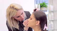 Model and make-up artist with eye-liner and model at work Stock Footage