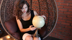Sexy girl with a globe in the armchair Stock Footage