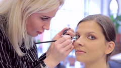 Beautifyl young girl and make-up attist with eye-liner Stock Footage