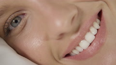 CLOSE UP: Beautiful young woman waking up in the morning with a smile on a face Stock Footage