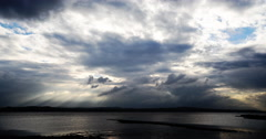 Sunbeams through moody clouds over water time-lapse Stock Footage
