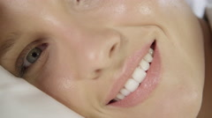 CLOSE UP: Gorgeous young woman waking up in the morning with a smile on a face Stock Footage