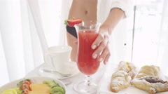 CLOSE UP: Girl taking glass of cocktail from table full of fruits and goodies Stock Footage