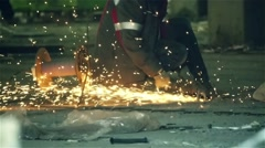 Builder cuts metal with a angle grinder on a construction site, slow motion Stock Footage