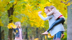 Happy family in autumn park enjoy warm day Stock Footage