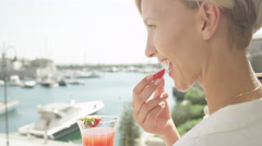 CLOSE UP: Woman eating fresh strawberry on terrace with view on sailboat harbor Stock Footage