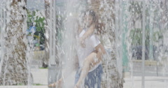 4K Happy couple having fun at water fountain in the city Stock Footage