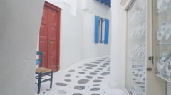 3 axis gimbal walking along a mykonos  street past shops Stock Footage