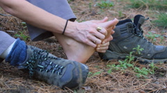 Female hiker rubs sore bare foot with hands. Hiking boot nearby. Arkistovideo