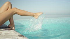 CLOSE UP: Young woman splashing water with her legs lying on the edge of pool Stock Footage
