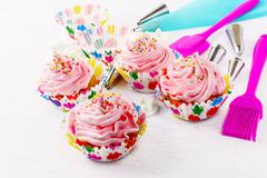 Cupcakes with pink whipped cream swirl and confectionery syringe Stock Photos