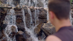Man relaxing near waterfall. Relaxation concept. Closeup of mans head Stock Footage