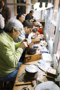 Artisan jewelers creating hand made jewelry items in a workshop. Stock Photos