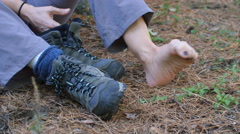Female hiker wiggles sore foot after hiking. Hiking boots nearby. Stock Footage