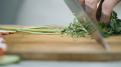 Chef cutting parsley in the kitchen with a sharp knife Stock Footage