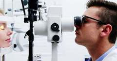 Optometrist examining female patient on slit lamp Stock Footage