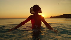 CLOSE UP: Pretty woman in swimming pool playing with water and watching sunset Stock Footage