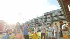 Happy people dancing and playing guitar at the rooftop party on sunny day Stock Footage