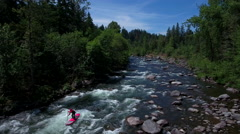 Aerial backtracking shot of paddle boarder going down river. Stock Footage