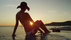 CLOSE UP: Pretty woman in swimming pool touching water surface, watching sunset Stock Footage