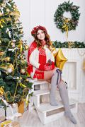Lovely girl in stockings at Christmas tree Stock Photos