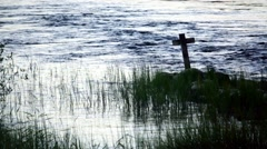 Wooden cross standing by a riverbank with sedge in evening light Stock Footage