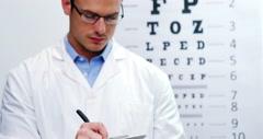 Optometrist writing on clipboard Stock Footage