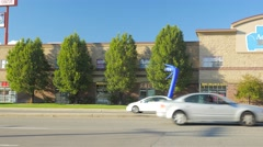 Tall blue wiggly advertizing man from across a busy street Stock Footage