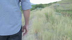 Handheld Follow of Man Walking Down Path Touch Weeds with his Hand Stock Footage