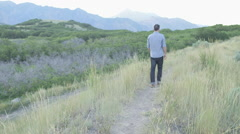 Wide Handheld of Man Walking Down Path Touching Weeds with Hand Stock Footage