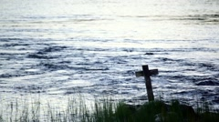 Wooden cross standing by a riverbank in evening light Stock Footage