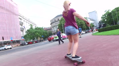 Low angle back view of women longboarding with friends in the city Stock Footage