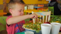 Young boy eating salad at a resturant Stock Footage
