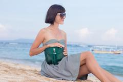Young slim sexy woman on the beach. Luxury handmade snakeskin in her hands Stock Photos