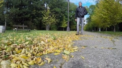 Man Walking in the Autumn Park on a Sunny Day Stock Footage