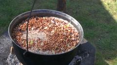 Porridge in pot boiling over fire Stock Footage