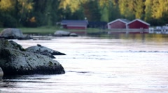 River streaming peacefully on a summer evening, boathouses in the background Stock Footage
