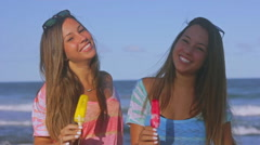 Twin Sisters Toasting Melting Popsicles In A Hot Summer Day Beach in Slow Motion Stock Footage