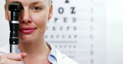 Female optometrist holding ophthalmoscope Stock Footage