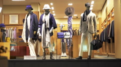 Silhouettes of pedestrians in front of Mannequins in window of shop. Looped Stock Footage