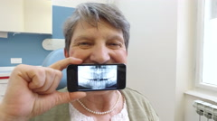 Close up of elderly woman holding smartphone with photo of dental X- ray Stock Footage