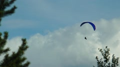 Paragliders soar over the forest on a background picturesque sky. Stock Footage