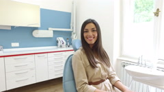 Smiling woman looking at camera while sitting in the dental chair Stock Footage