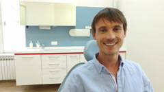 Young man with healthy white teeth smiling and looking at camera at dentist Stock Footage