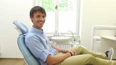 Man with beautiful white smile sitting in dental chair and looking at camera Stock Footage