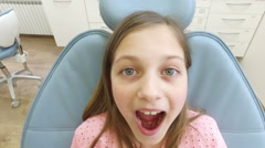 Close up of little girl sitting in the dental chair with open mouth Stock Footage