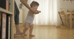 Cute Baby Walking With His Mothers Help Stock Footage