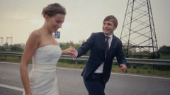 Bride and groom running at the rain Stock Footage