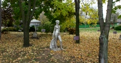 "The sculpture ""Nude with shawl"" in the autumn Park of modern art, yellow leaves Stock Footage"